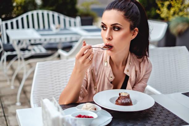 brünette mädchen essen souffle auf der restaurantterrasse - make up torte stock-fotos und bilder