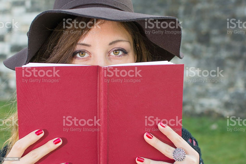 Brunette girl holding a red book stock photo