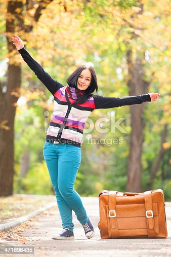 istock Brunette girl holding suitcase at autumn alley in the park 471896435