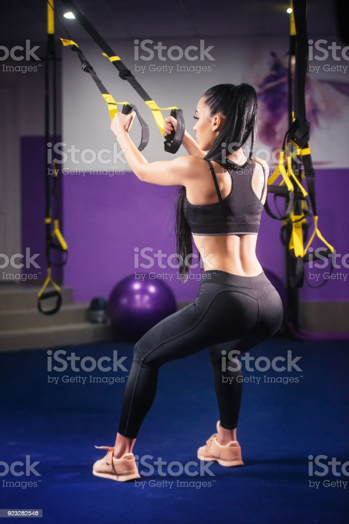 Brunette girl in Electrical Muscular Stimulation suit doing squat exercise for back and with suspension. stock photo