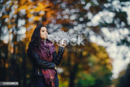 istock brunette girl is smoking an e-cigarette 1049099626
