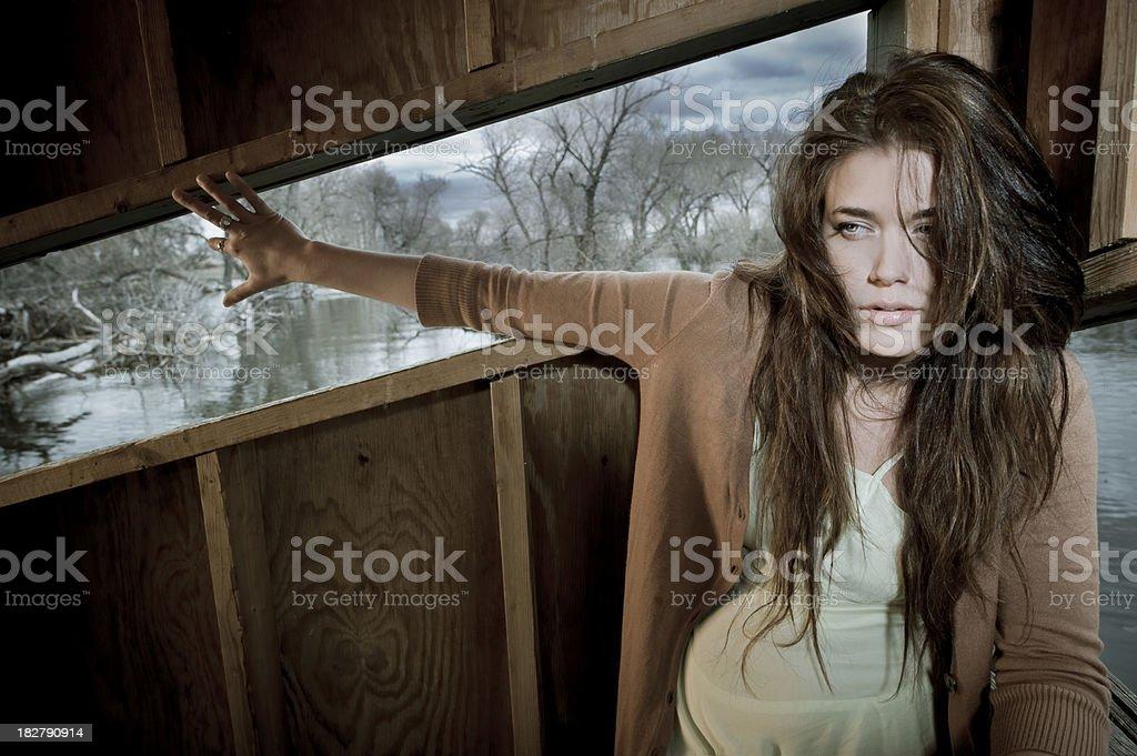 Brunette Girl Looks Away against Wood Wall stock photo