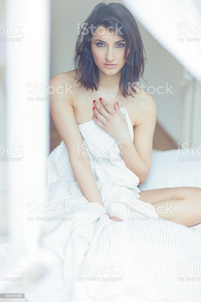 Brunette girl on white sheets royalty-free stock photo