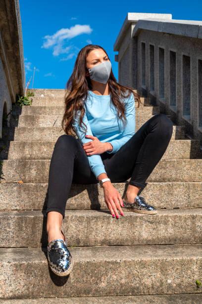Brunette girl posing with luxury fashion face mask due coronavirus COVID-19 protection stock photo