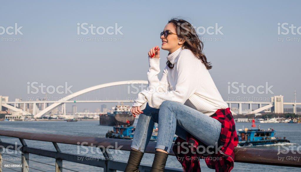 Chica morena sentada junto al río foto de stock libre de derechos