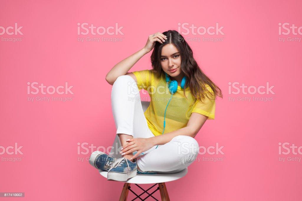 Menina morena sentada na cadeira, tocando a cabeça - foto de acervo