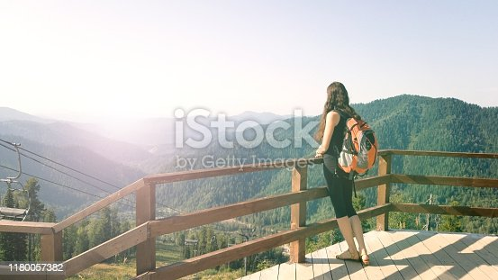 istock A brunette girl stands on an observation deck in the mountains and admires the beautiful view. A traveler with a backpack resting on the top of the mountain. Excursion to the Altai mountains. Dreamy and free concept 1180057382
