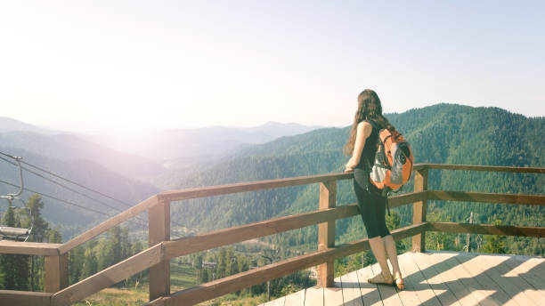 a brunette girl stands on an observation deck in the mountains and admires the beautiful view. a traveler with a backpack resting on the top of the mountain. excursion to the altai mountains. dreamy and free concept - altai nature reserve стоковые фото и изображения