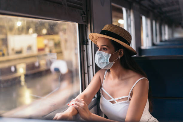 Brunette girl traveler on train in a face mask and summer clothes looking out the window stock photo