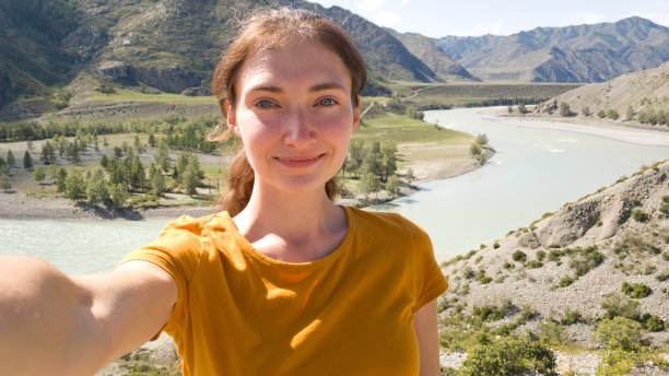 donkerbruin meisje met een paardenstaart. neemt een selfie op de achtergrond van de rivier. zomerreis in de natuur. een reis naar de altai - altai nature reserve stockfoto's en -beelden