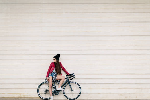Brunette girl with very long hair and dressed in red leather jacket, waiting sitting on her black urban bike