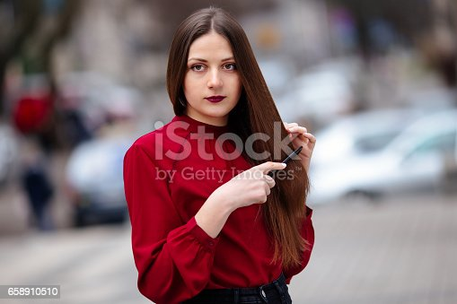 625205382 istock photo Brunette hair woman brushing her hair with brush and smiling 658910510