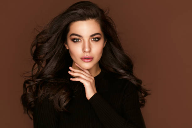 갈색 머리 여자 초상화 와 파란 눈과 건강 한 긴 빛나는 물결 모양 헤어 스타일 볼륨 샴푸. 블랙 곱슬 파마 머리와 밝은 메이크업.  뷰티 살롱과 헤어 케어 개념. - 붙임 머리 뉴스 사진 이미지