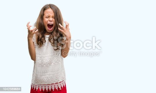 istock Brunette hispanic girl crazy and mad shouting and yelling with aggressive expression and arms raised. Frustration concept. 1042589684
