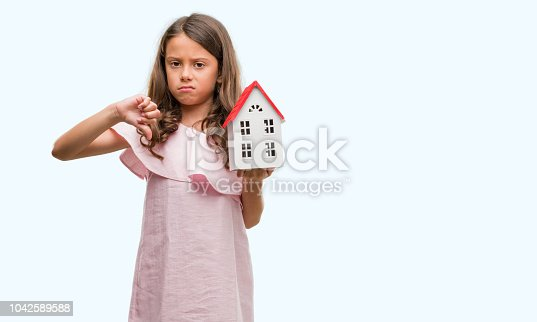 Brunette hispanic girl holding little house with angry face, negative sign showing dislike with thumbs down, rejection concept