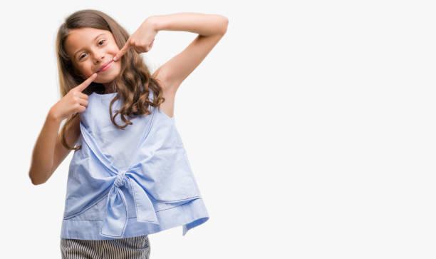 morena garota hispânica sorrindo mostrando confiante e apontando com boca e dentes de dedos. conceito de saúde. - dedo termo anatômico - fotografias e filmes do acervo