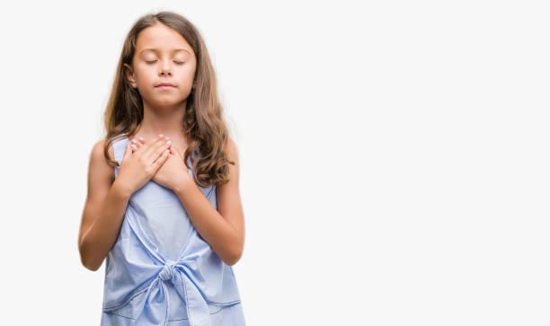 brünette hispanischen mädchen mit händen auf brust mit geschlossenen augen und dankbar geste auf gesicht lächelnd. gesundheitskonzept. - die wahrheit tut weh stock-fotos und bilder