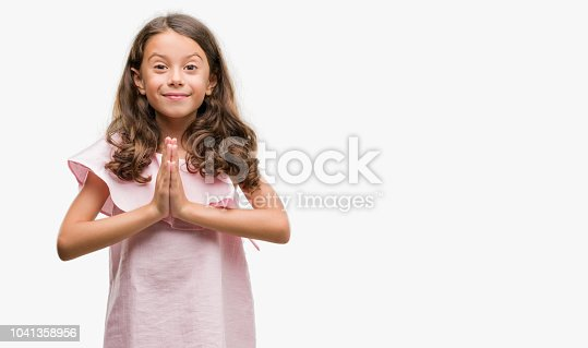 Brunette hispanic girl wearing pink dress praying with hands together asking for forgiveness smiling confident.