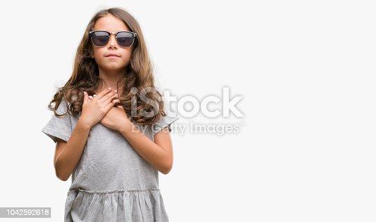 c74f145dee 1042592618istock Chica hispana morena con gafas de sol con las manos en el  pecho con los