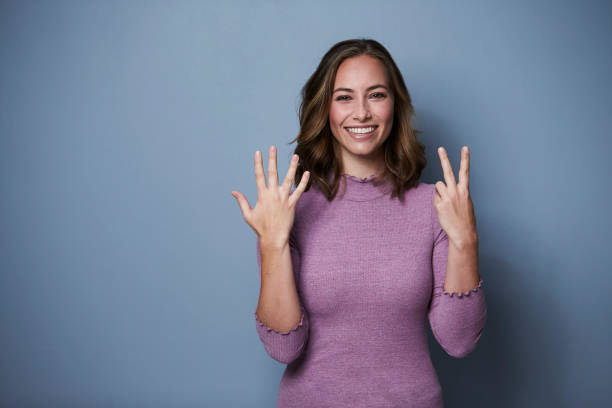 Brunette holding seven fingers Beautiful woman using fingers to show seven, studio number 7 stock pictures, royalty-free photos & images