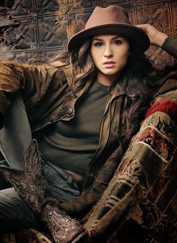 beautiful brunette holding onto hat
