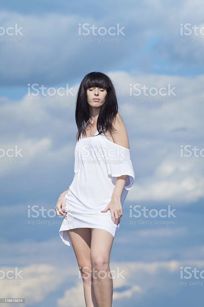 Brunette in white on background of sky royalty-free stock photo