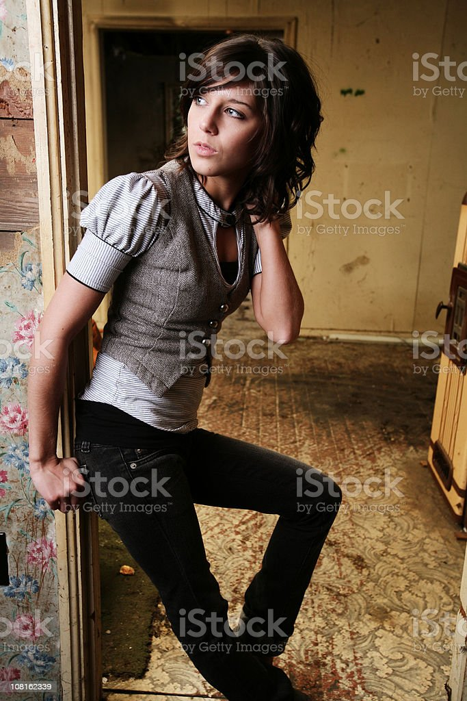 Brunette Leaning Against Door Frame in Old House royalty-free stock photo