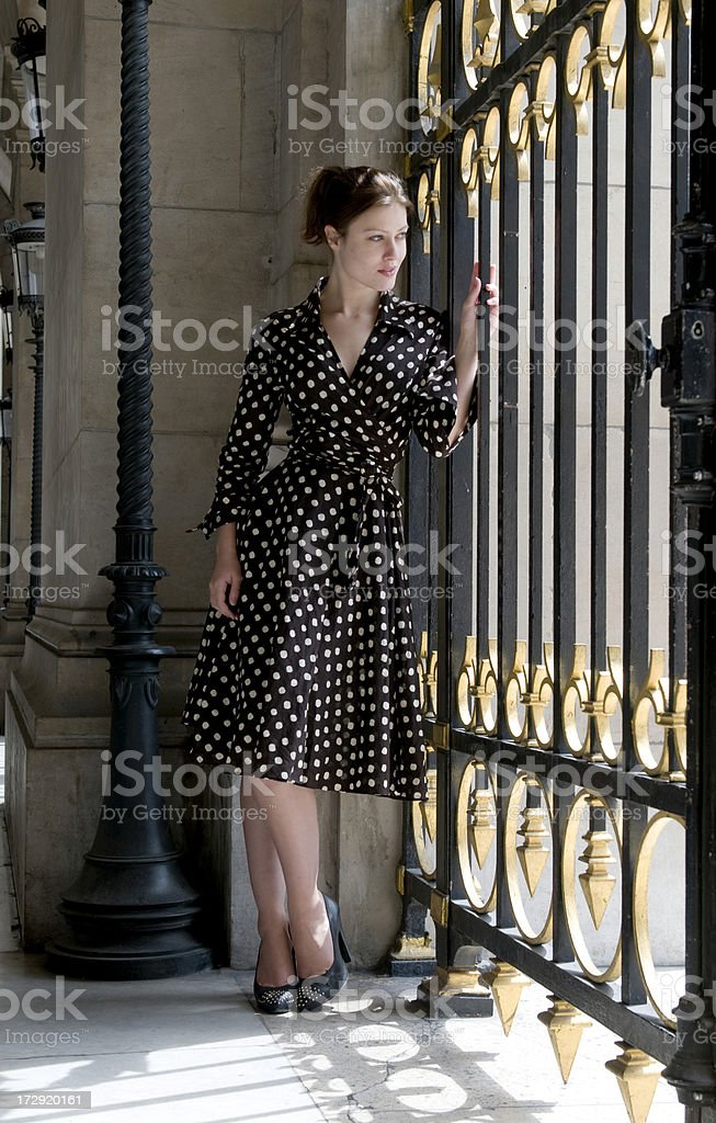 Brunette leaning against gate waiting for someone royalty-free stock photo