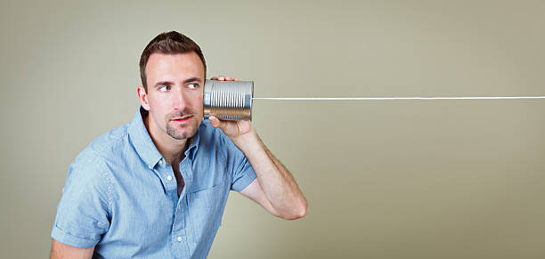 Brunette man in blue shirt listening to a tin can telephone