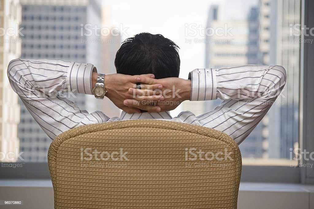 A brunette man sitting back pleased with himself stock photo