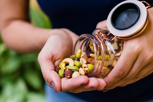 Brunette model hand holding glass hermetic pot with mix of nuts.
