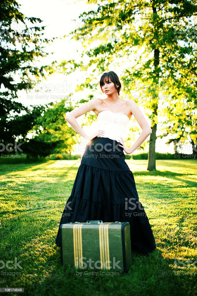 Brunette Model in Big Dress with Green Suitcase royalty-free stock photo