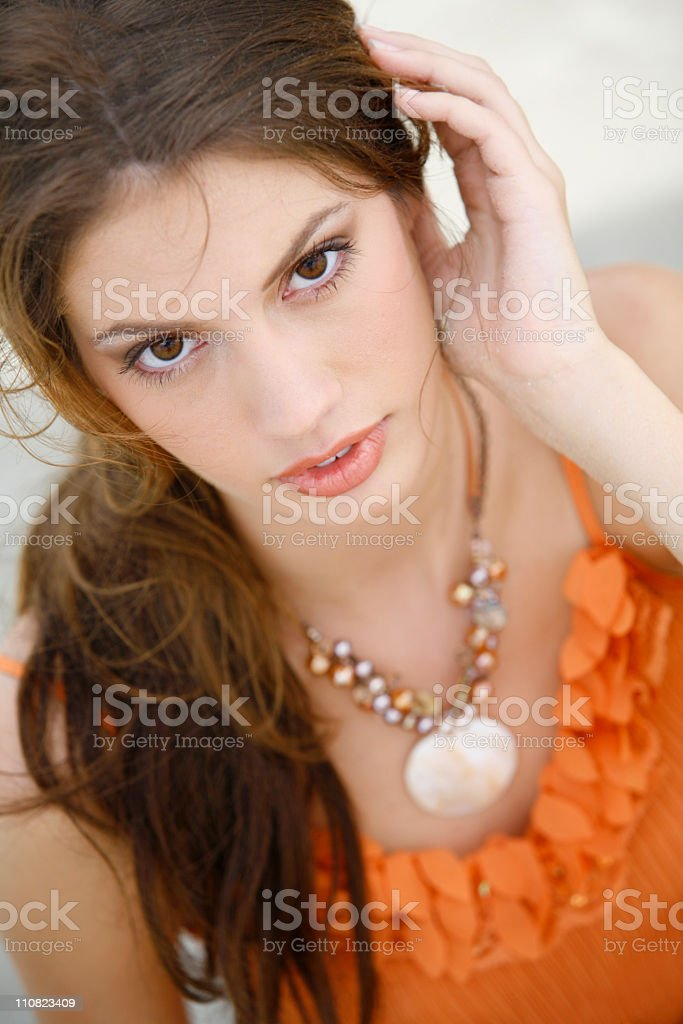 Brunette model looking at camera in a orange top royalty-free stock photo
