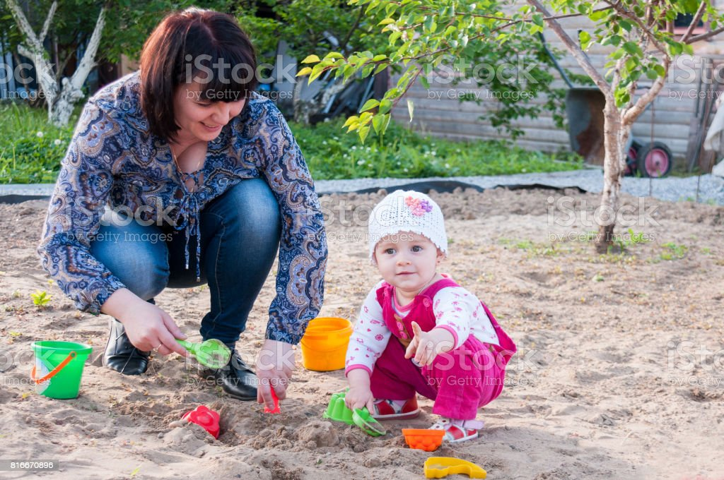 Brunette Mom Playing With Her Baby In The Sandbox Royalty Free Stock Photo