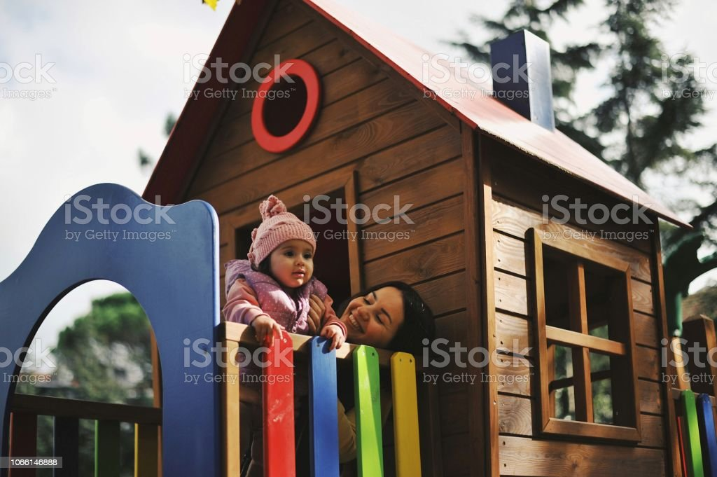 Brunette mom spending time with her little baby girl at a park stock photo