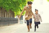 Brunette mother daughter walking in Paris park on spring afternoon