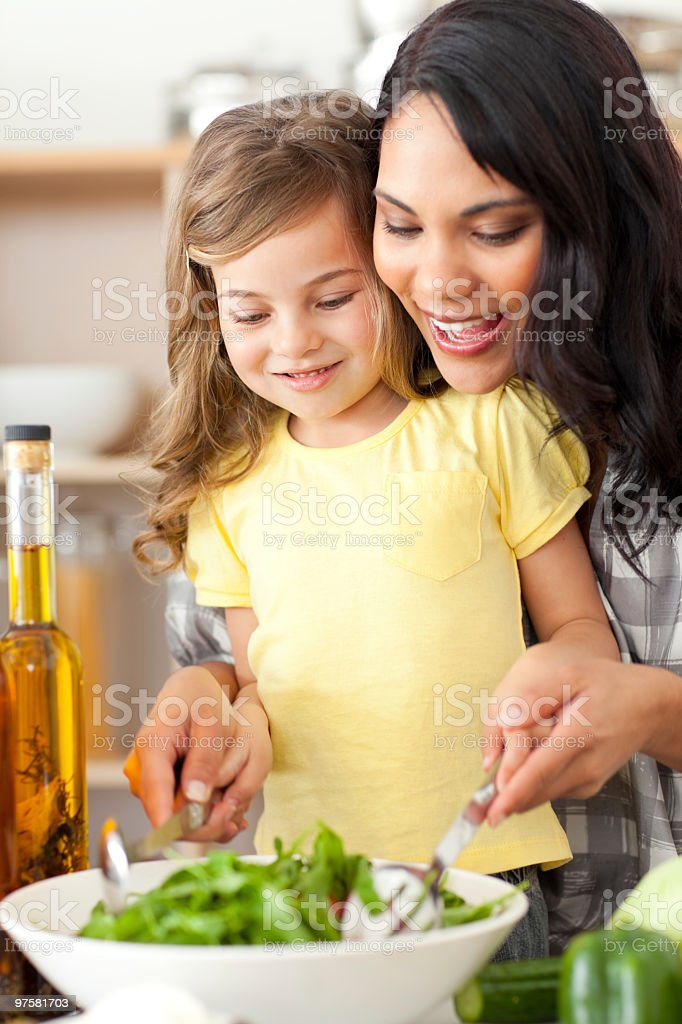 Brunette mother helping her daughter prepare salad royalty-free stock photo