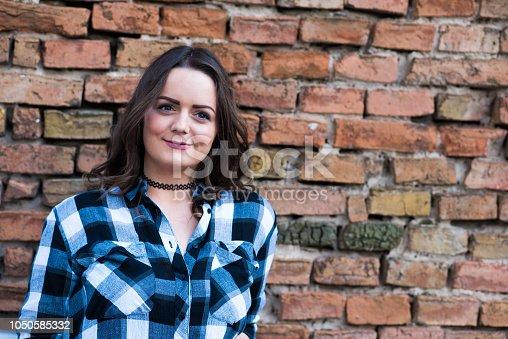 Happy brunette girl near old bricks wall awaiting a meeting.