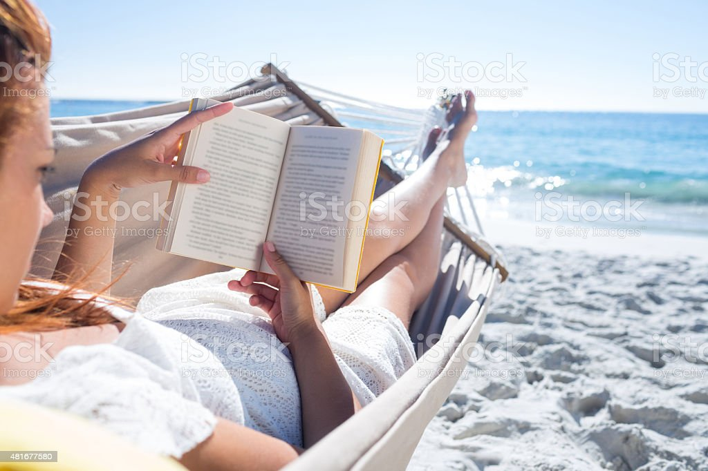 Brunette reading a book while relaxing in the hammock stock photo