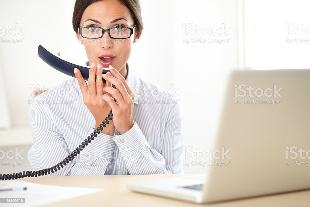 Brunette secretary talking to the phone royalty-free stock photo