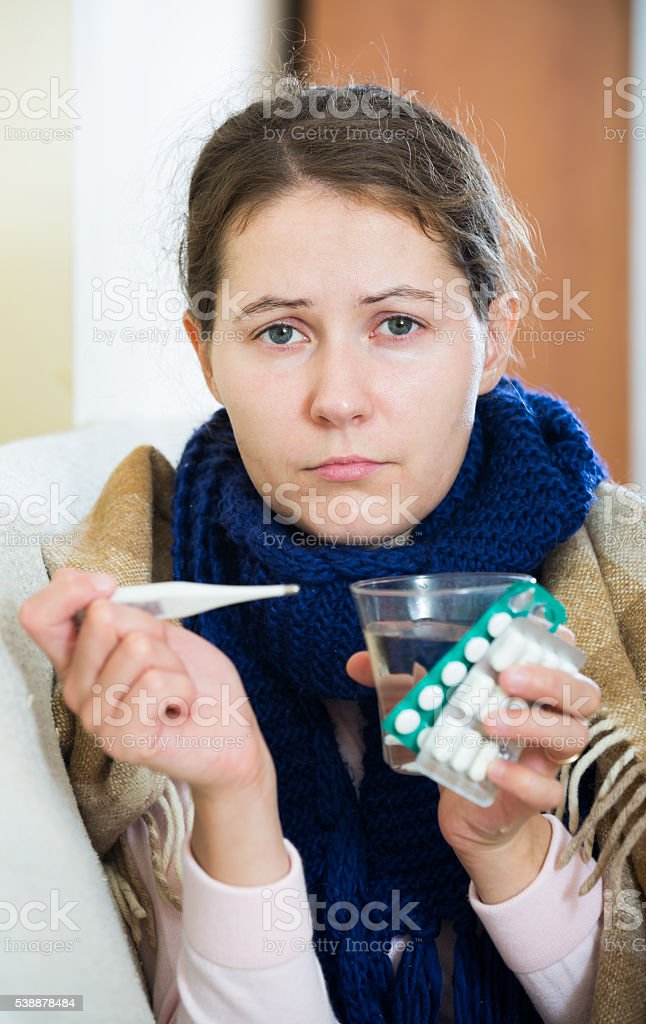brunette sick with fever under blanket in domestic interior stock photo