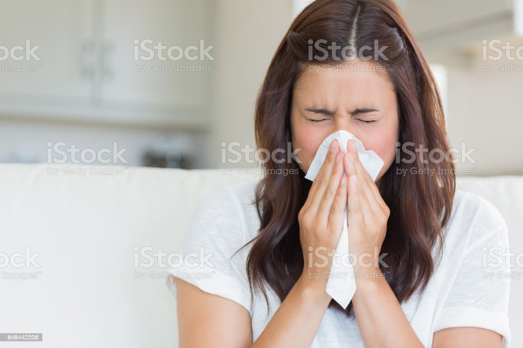 Brunette sneezing in a tissue stock photo