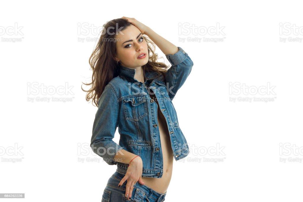 Brünette steht seitlich in eine Jeansjacke und blickt in eine Kamera Lizenzfreies stock-foto