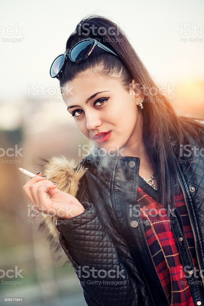 brunette stylish teenage girl smoking cigarette at sunset royalty free stock photo