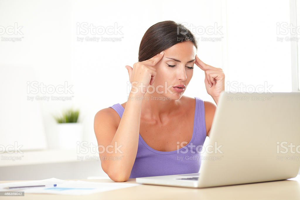 Brunette tired female working on her laptop royalty-free stock photo