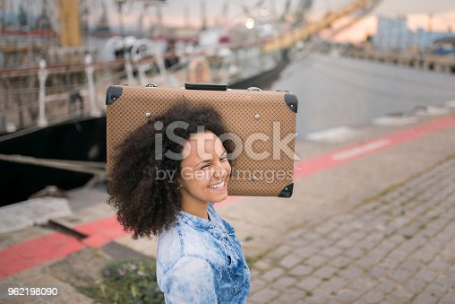 Brunette traveler laughing with suitcase on shoulder. Strolling around Port of Varna, Bulgaria during the summer.