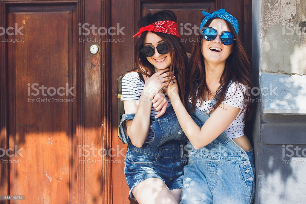Brunette twins sisters hugging and laughing. Having fun. Copy space. stock photo