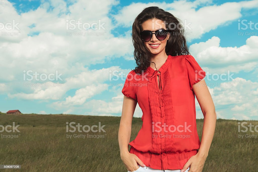 brunette wearing red blouse poses hands in pockets stock photo