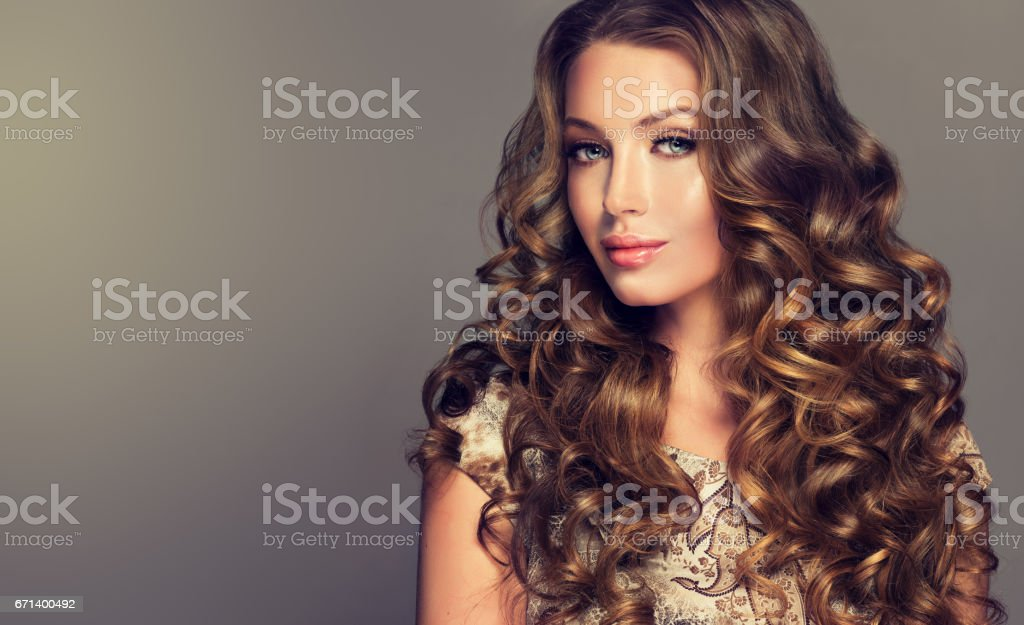 Brunette with voluminous, shiny and curly hairstyle. stock photo