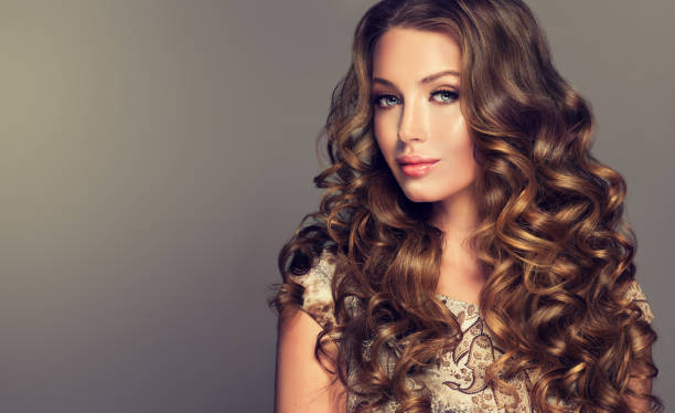Brunette with voluminous, shiny and curly hairstyle. – Foto